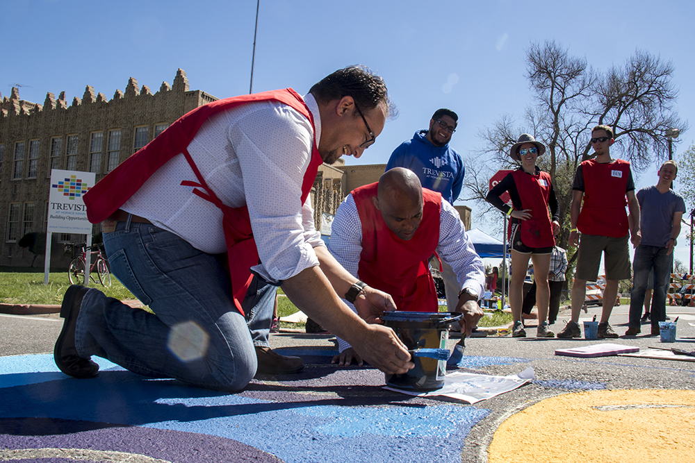 Mayor Michael Hancock and City Councilman Rafael Espinoza, fully-smocked, paint a mural on the street. May 13, 2017. (Kevin J. Beaty/Denverite)  walk denver; sunnyside; trevista at horace mann; kevinjbeaty; denver; colorado; public art; mural;