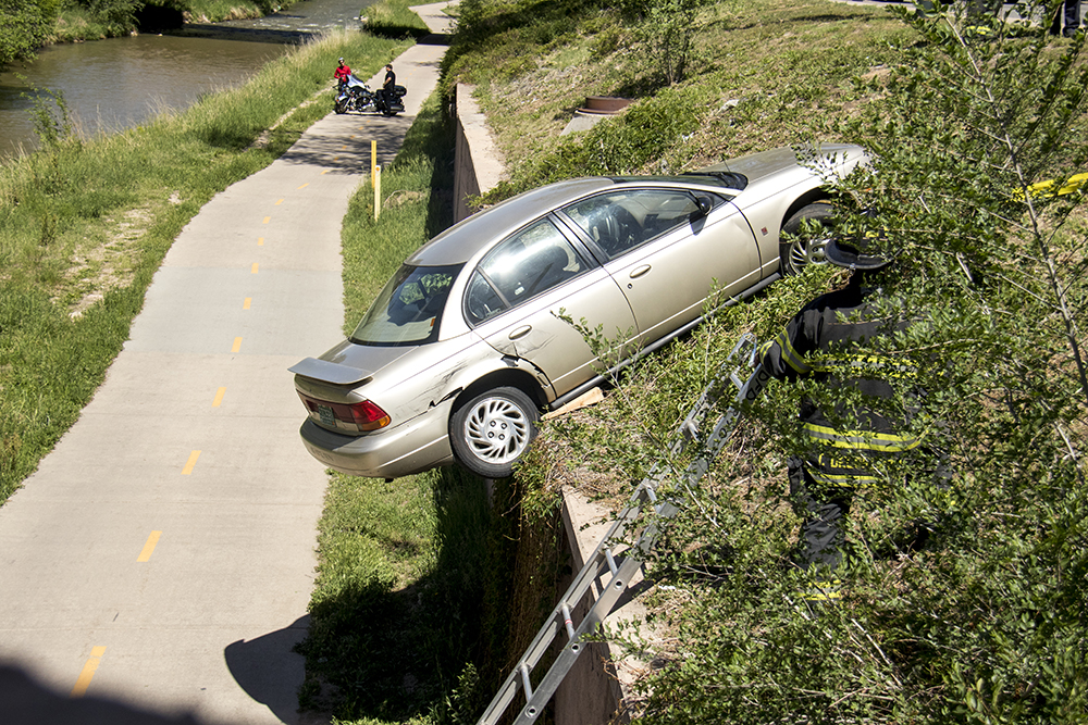 A car that has been spun off the road and almost into the Cherry Creek Trail near Speer Boulevard and 8th Avenue. (Kevin J. Beaty/Denverite)