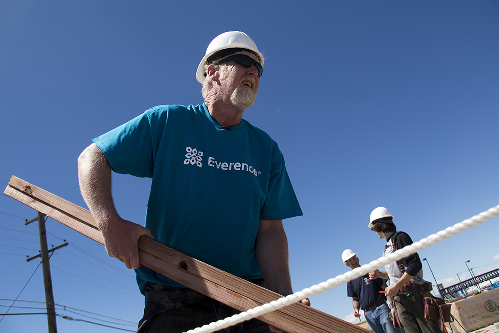 Future resident Chris Ollar picks up a beam. Construction on the Beloved Community Village begins at Walnut and 38th streets, May 20, 2017. (Kevin J. Beaty/Denverite)  homeless; right to rest; tiny home village; rino; five points; denver; denverite; colorado; kevinjbeaty;