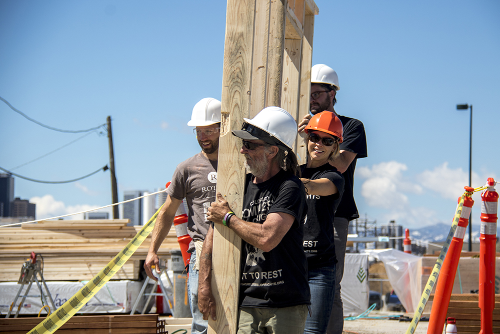 """Right to rest"" advocate Ray Lyall leads a team carrying a newly-completed frame. Construction on the Beloved Community Village begins at Walnut and 38th streets, May 20, 2017. (Kevin J. Beaty/Denverite)  homeless; right to rest; tiny home village; rino; five points; denver; denverite; colorado; kevinjbeaty;"