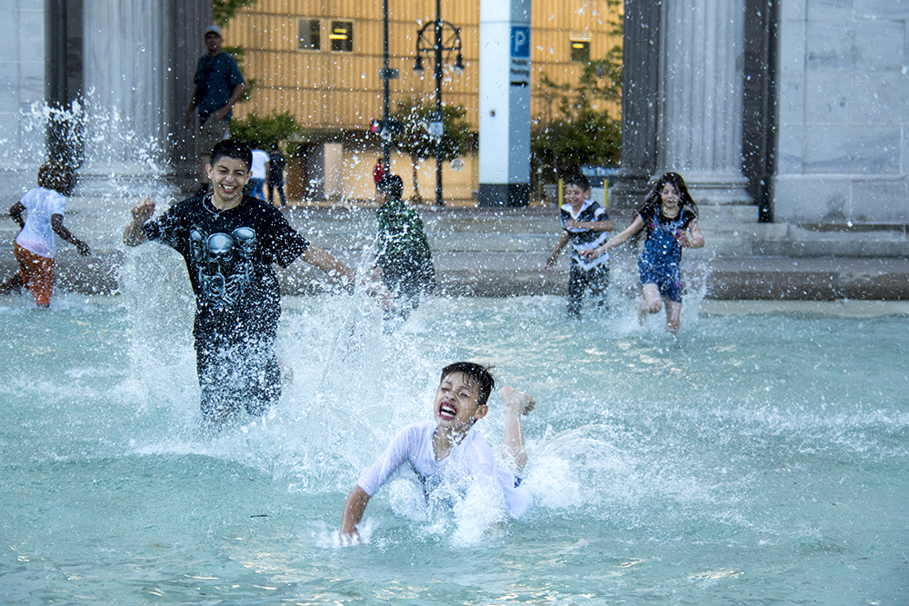 A kid named Moses swims in a fountain at Civic Center Park, May 25, 2017. (Kevin J. Beaty/Denverite)  summer; cowx; weather; civic center park; denver; denverite; colorado; kevinjbeaty