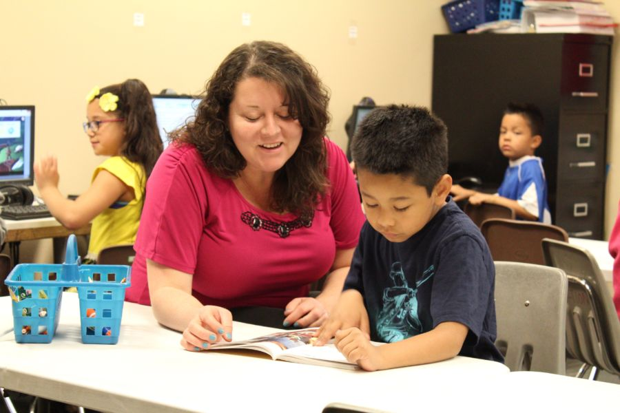 Ana Gramajo, left, is the co-director of HOPE Online Action Academy in Aurora. Here she works with a student on reading. (Nicholas Garcia/Chalkbeat)