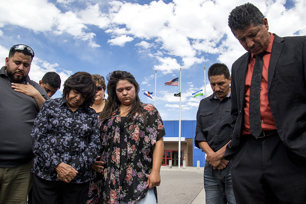 Isidro Quinana's family and church prays outside of the GEO private detention facility after his deportation order was cancelled, May 15, 2017. (Kevin J. Beaty/Denverite)  isidro quintana; aurora; GEO; immigration; deportation; kevinjbeaty; denverite; colorado