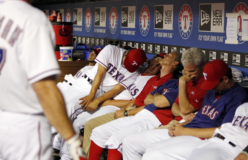 "Rangers players ""sleep"" in the dugout in a 2013 game. (Tim Heitman/USA Today Sports)"