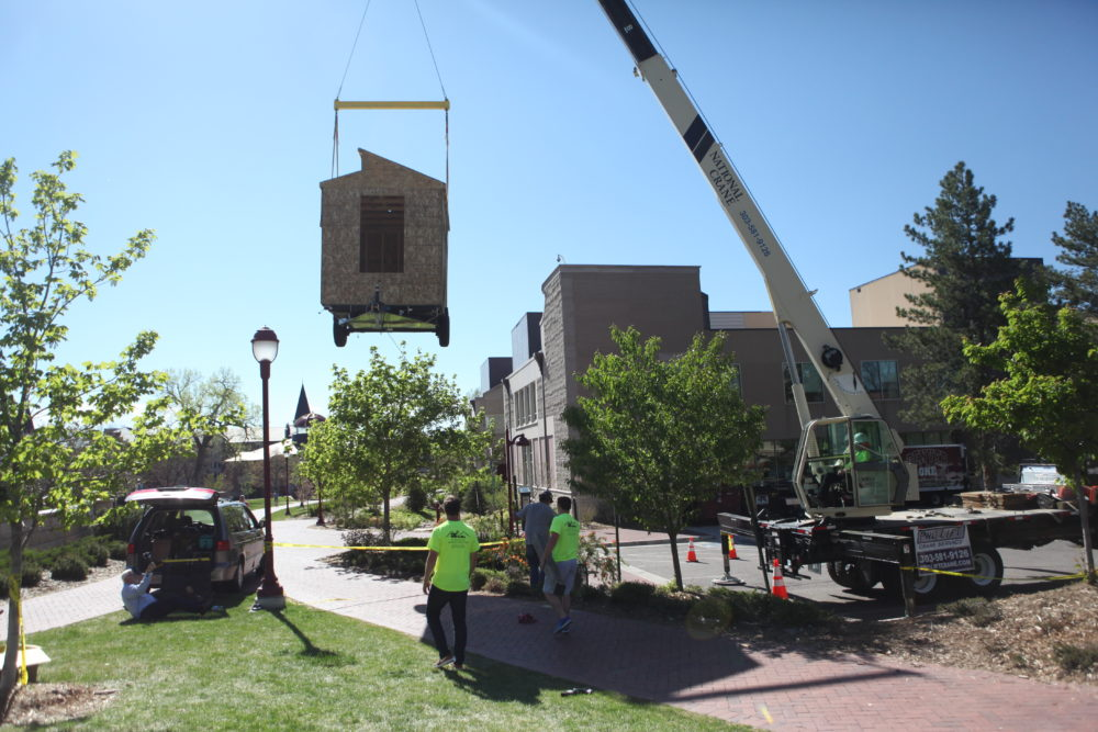 A Pro Lift crew hoists a framed-out tiny home at the University of Denver on May 5, 2017. (Andrew Kenney/Denverite)
