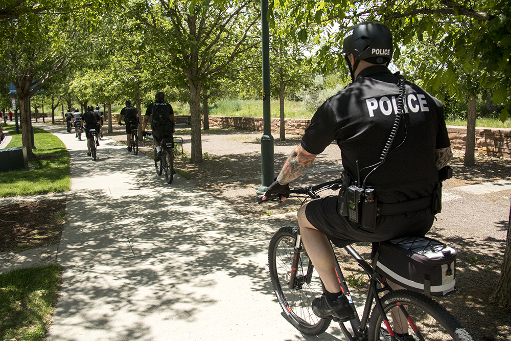 Denver Police ride bikes around Commons Park during the March for Truth, June 3, 2017. (Kevin J. Beaty/Denverite)
