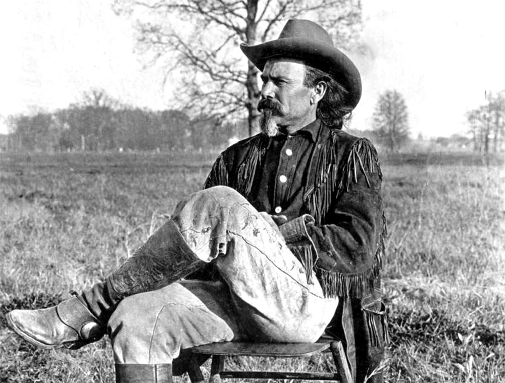 William Frederick Cody (Buffalo Bill) sits in a folding chair in a pasture. He wears boots, spurs, and embroidered leather pants and a leather jacket with fringe, circa 1900. (Denver Public Library/Western History Collection/Z-7554)  denver public library; buffalo bill; wild west; colorado;