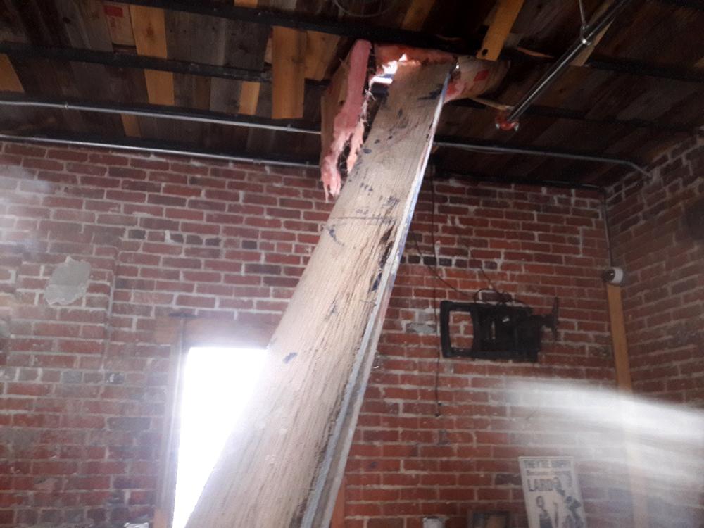 A wooden board through the roof of The Grateful Gnome in Denver's Berkeley neighborhood, June 13, 2017. (Adrian D. Garcia/Denverite)
