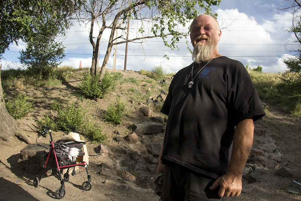 Gary Duncan, who prefers not to stay at the Crossroads homeless shelter, hanging out in the shade by the South Platte River, June 14, 2017. (Kevin J. Beaty/Denverite)