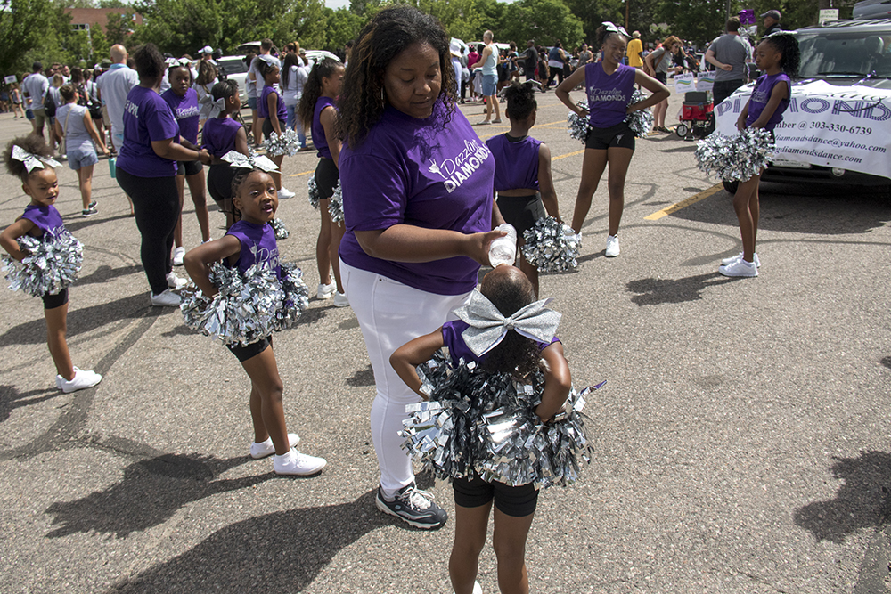 Dazzling Diamonds Coach Amber Adams feeds water to 5 year old Jahnayla so she doesn't mess up her makeup. The Juneteenth parade in Five Points, June 17, 2017. (Kevin J. Beaty/Denverite)juneteenth; five points; black history; kevinjbeaty; denver; colorado; denverite; street fair; festival; welton street;