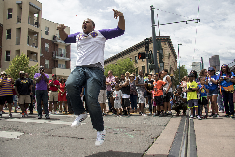 Danny Perkins gets airborne as the Omega Psi Phi Fraternity crosses Welton Street. The Juneteenth parade in Five Points, June 17, 2017. (Kevin J. Beaty/Denverite)
