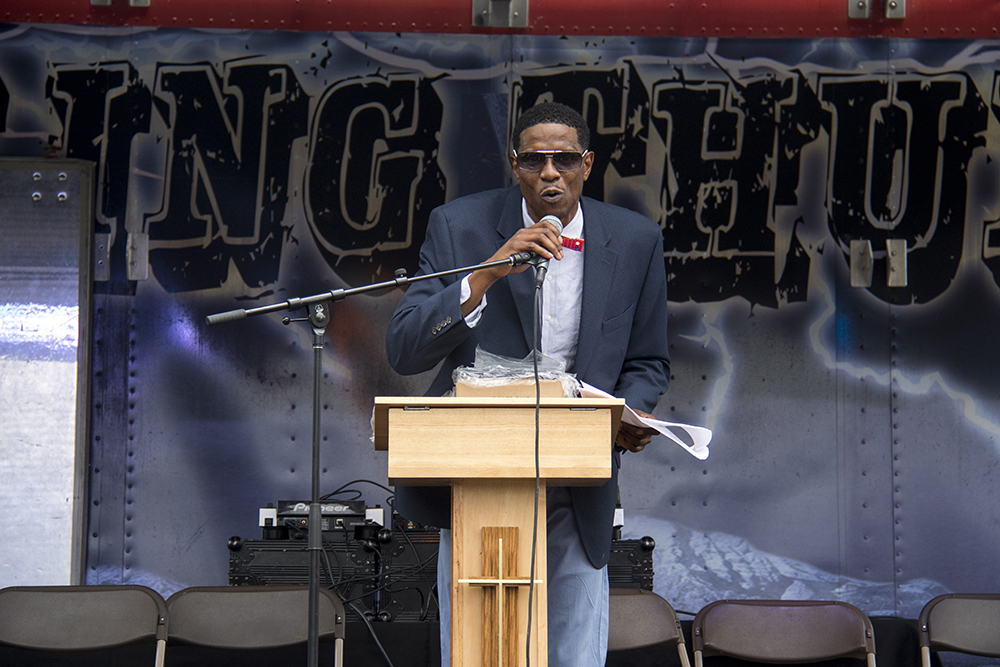 """Norman Harris III beckons audiences to wat1ch """"dream big"""" honorees accept awards. Juneteenth in Five Points, June 17, 2017. (Kevin J. Beaty/Denverite)"""