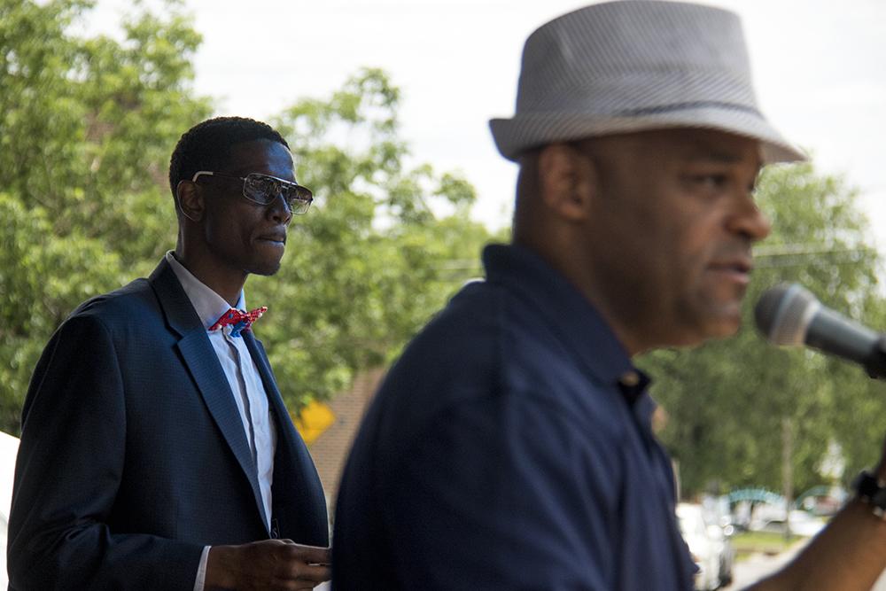 "Norman Harris III watches Mayor Hancock address the crowd on stage for the first annual ""dream big"" awards. Juneteenth in Five Points, June 17, 2017. (Kevin J. Beaty/Denverite)  juneteenth; five points; black history; kevinjbeaty; denver; colorado; denverite; street fair; festival; welton street;"