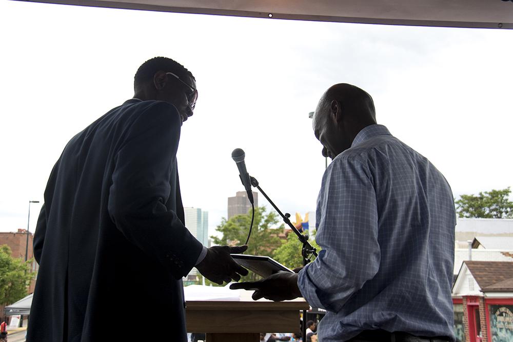 "Norman Harris III presents Brother Jeff Fard with a ""dream big"" award. Juneteenth in Five Points, June 17, 2017. (Kevin J. Beaty/Denverite)  juneteenth; five points; black history; kevinjbeaty; denver; colorado; denverite; street fair; festival; welton street;"