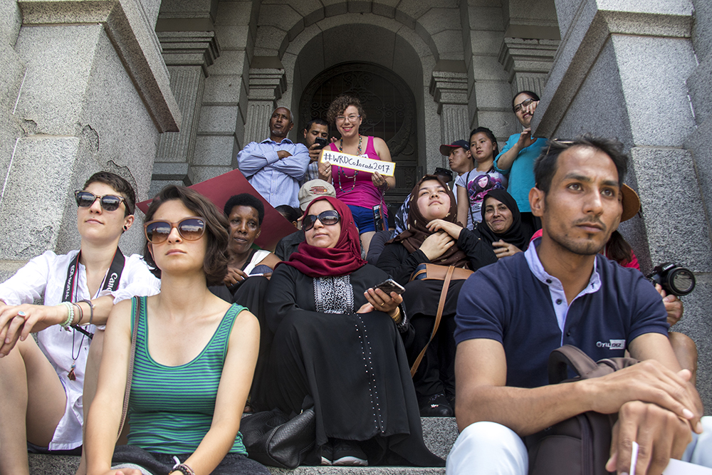 Refugees and allies sit on the Capitol steps before Governor John Hickenlooper takes the stage during World Refugee Day, June 20, 2017. (Kevin J. Beaty/Denverite)