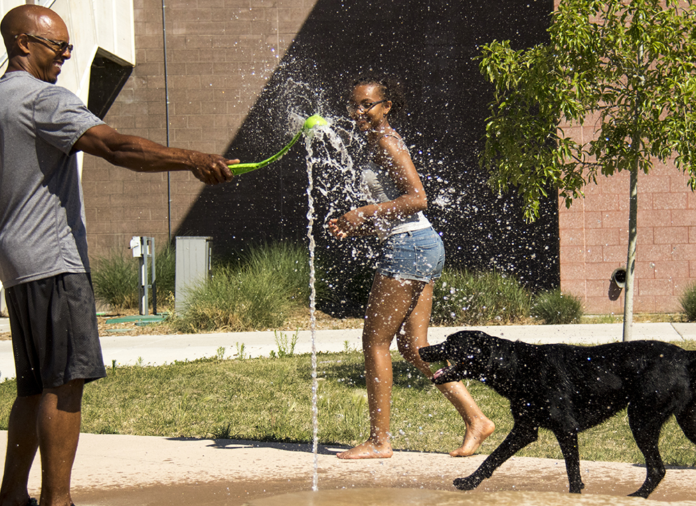 Martin Baughman throws a tennis ball to his dog Dakota through the Montbello Recreation Center's fountains. (Kevin J. Beaty/Denverite)  montbello; denver; denverite; colorado; kevinjbeaty;