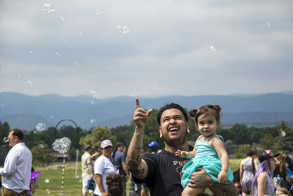 Terek Milligan and his daughter Paige behold a skyful of bubbles. The first-annual Unicorn Festival in Clement Park, Littleton. (Kevin J. Beaty/Denverite)  colorado; kevinjbeaty; unicorn festival; denverite; littleton; whimsy; summer;