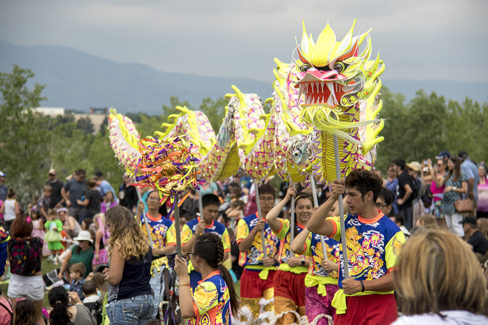 Performers from the Colorado Asian Culltural Heritage Center leads a dragon through the audience. The first-annual Unicorn Festival in Clement Park, Littleton. (Kevin J. Beaty/Denverite)  colorado; kevinjbeaty; unicorn festival; denverite; littleton; whimsy; summer;