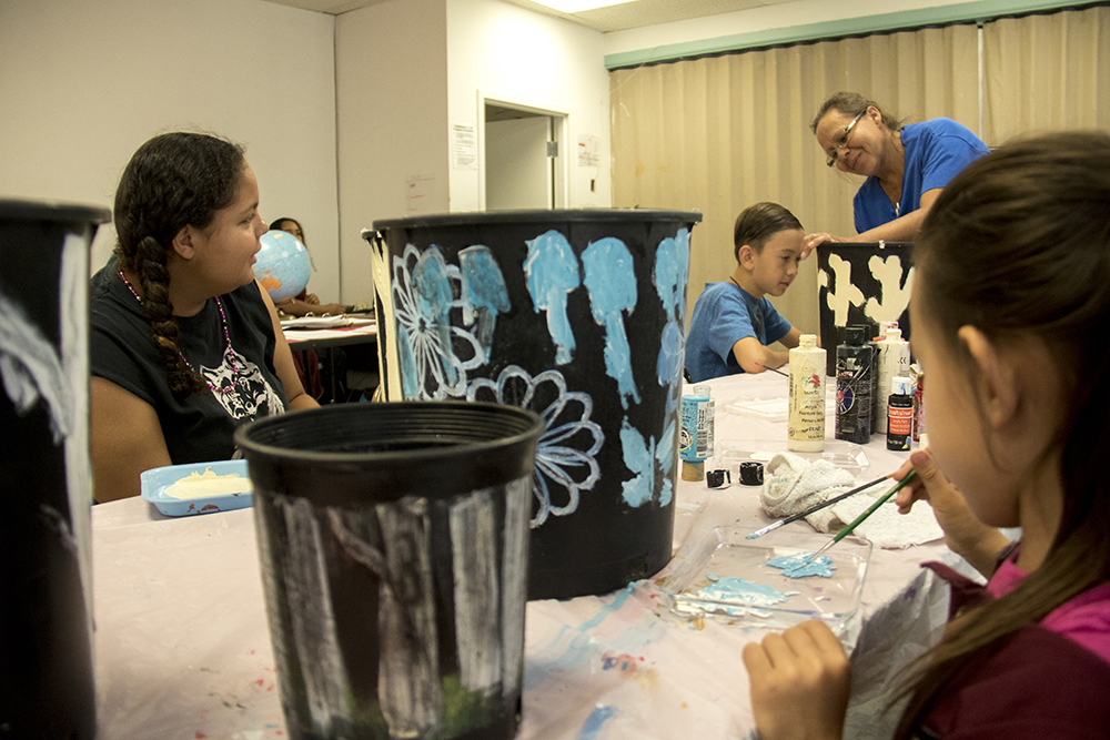 Gwyndalyn (left to right), Mathew, instructor Gwyneth Chavez and Vanessa paint flower pots during art class at the Denver Indian Center. (Kevin J. Beaty/Denverite)  denverite; colorado; denver; denver indian center; westwood; kevinjbeaty;