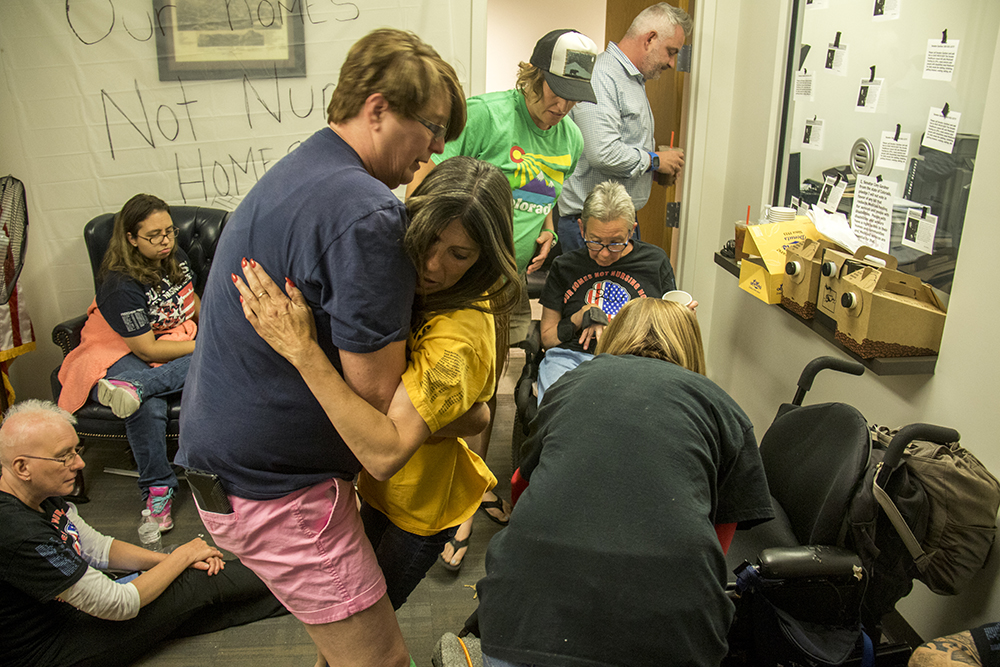Jan Parton helps Dawn Russell up from her wheelchair. A sit-in at Senator Cory Gardner's office opposing a Republican healthcare plan, June 28, 2017. (Kevin J. Beaty/Denverite)  denverite; protest; cory gardner; sit in; civil disobedience; healthcare; medicaid; kevinjbeaty; denver; colorado;