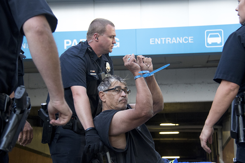 LB Smith is wheeled into the parking garage in ziptie cuffs. (Kevin J. Beaty/Denverite)
