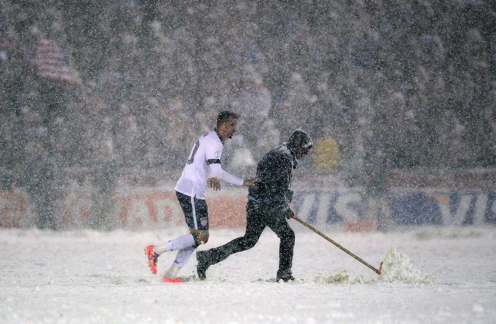 Geoff Cameron helps a grounds crew member shovel snow. (USA Today Sports)