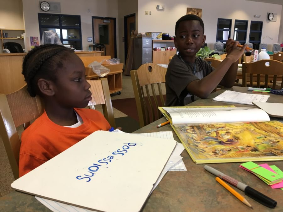 "Greenwood students Ja'zione and Arinze practice spelling the word ""possessions"" at the Each One Teach One literacy program. (Marissa Page/Chalkbeat)"
