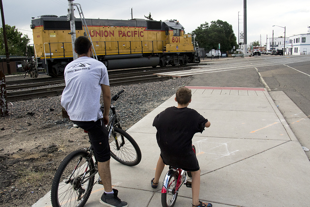 Modesto and Noah carefully cross train tracks crossing Josephine Street in Elyria-Swansea. (Kevin J. Beaty/Denverite)  elyria swansea; denver; denverite; colorado; kevinjbeaty;