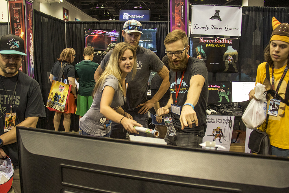 Second Wind Interactive co-founder Justin Larrabee (right) shows some passers-by his company's new virtual reality video game. Denver Comic Con, July 1, 2017. (Kevin J. Beaty/Denverite)  denver comic con; denverite; kevinjbeaty; denver; colorado; video games;