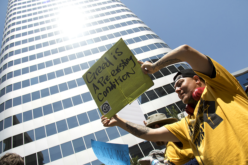 Anthony Logan holds up a sign beneath the building containing Sen. Cory Gardner's office. A protest against a Republican Healthcare bill at Skyline Park, July 6, 2017. (Kevin J. Beaty/Denverite)  healthcare; copolitics; politics; adapt; protest; skyline park; denverite; colorado; kevinjbeaty;