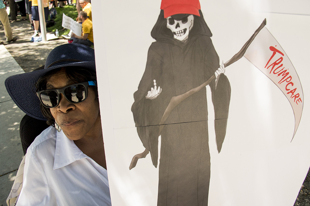 Vivian Stovall holds a sign bearing a grim reaper in a familiar red hat. A protest against a Republican Healthcare bill at Skyline Park, July 6, 2017. (Kevin J. Beaty/Denverite)  healthcare; copolitics; politics; adapt; protest; skyline park; denverite; colorado; kevinjbeaty;