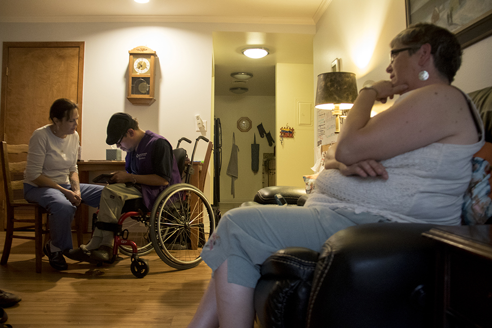 Aaron Walbert, his caretaker, Jennifer Hill, and his mother, Renee (right), at home in Capitol Hill, July 6, 2017. (Kevin J. Beaty/Denverite)  healthcare; medicaid; denver; capitol hill; denverite; colorado; kevinjbeaty; disability;