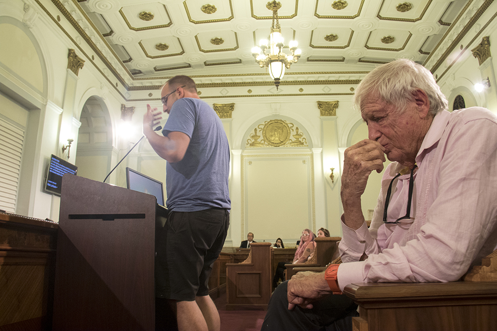 Developer Mickey Zeppelin listens as Nick LoVuolo addresses Denver City Council on 17-0726, a bill that aims to help legitimize DIY art spaces. (Kevin J. Beaty/Denverite)  diy art space; rhinoceropolis; meow wolf; denver city council; denverite; colorado; kevinjbeaty;