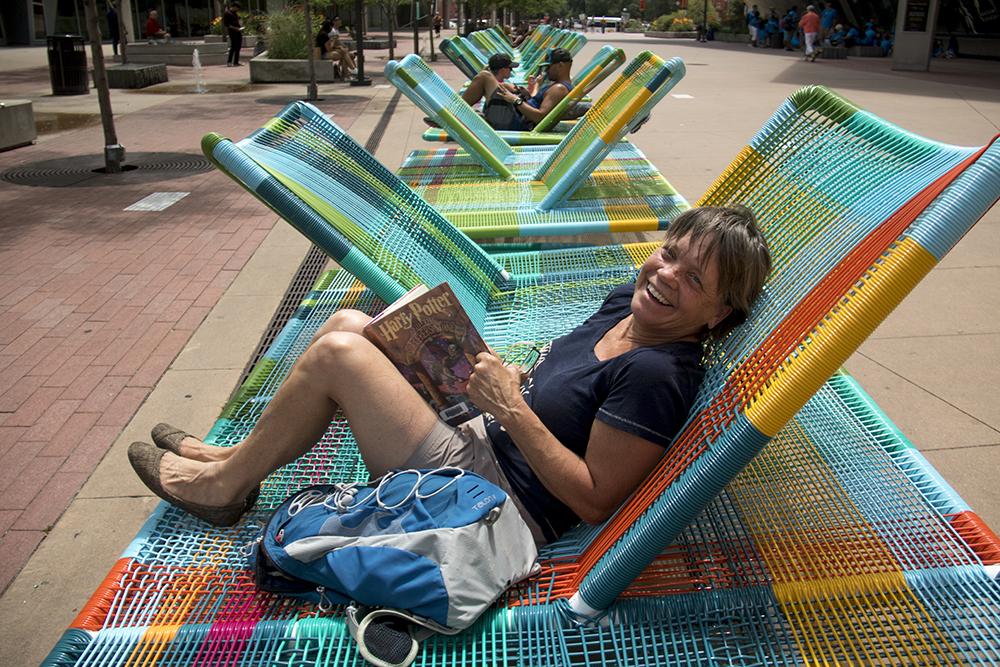 Karen Utke enjoys a musical recliner and the first installment of Harry Potter in front of the Denver Art Museum. (Kevin J. Beaty/Denverite)  dam; denver art museum; public art; kevinjbeaty; civic center; denverite; denver; colorado