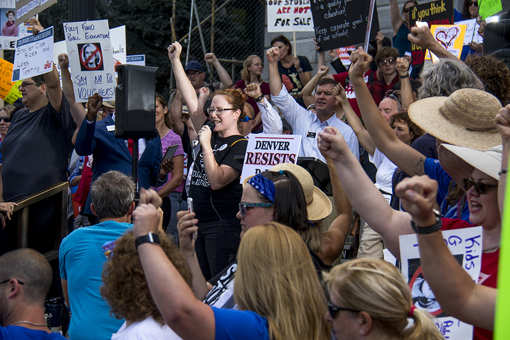 Denver Public Schools teacher Andrea Leggett holds up a fist as she addresses the crowd. A protest against U.S. Secretary of Education Betsy DeVos, who is scheduled to speak at an American Legislative Exchange Council this week. July 19, 2017. (Kevin J. Beaty/Denverite)  denver; colorado; denverite; kevinjbeaty; betsy devos; copolitics; protest; capitol; education;