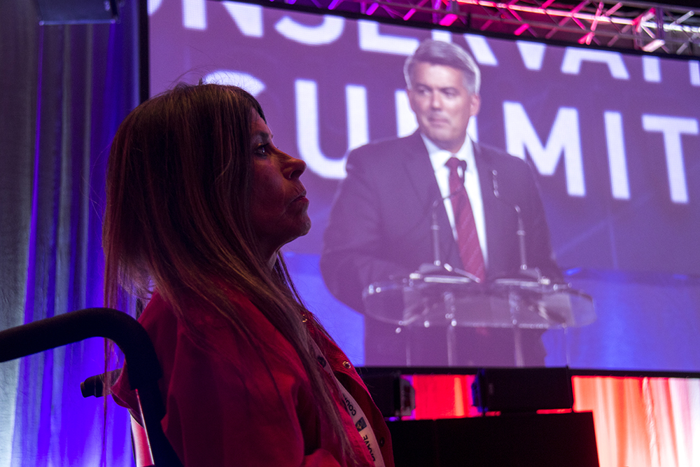 Dawn Russell watches Cory Gardner speak at the Western Conservative Summit, July 21, 2017. (Kevin J. Beaty/Denverite)  western conservative summit; wcs; protest; cory gardner; healthcare; adapt; medicaid; denver; denverite; kevinjbeaty;