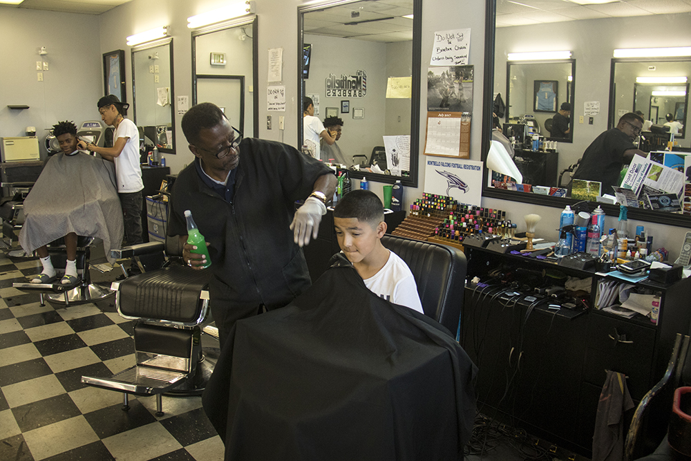 Chuck Sagere freshens up 11-year-old Adrian's hairline at his shop, Montbello Barbers, July 25, 2017. (Kevin J. Beaty/Denverite)
