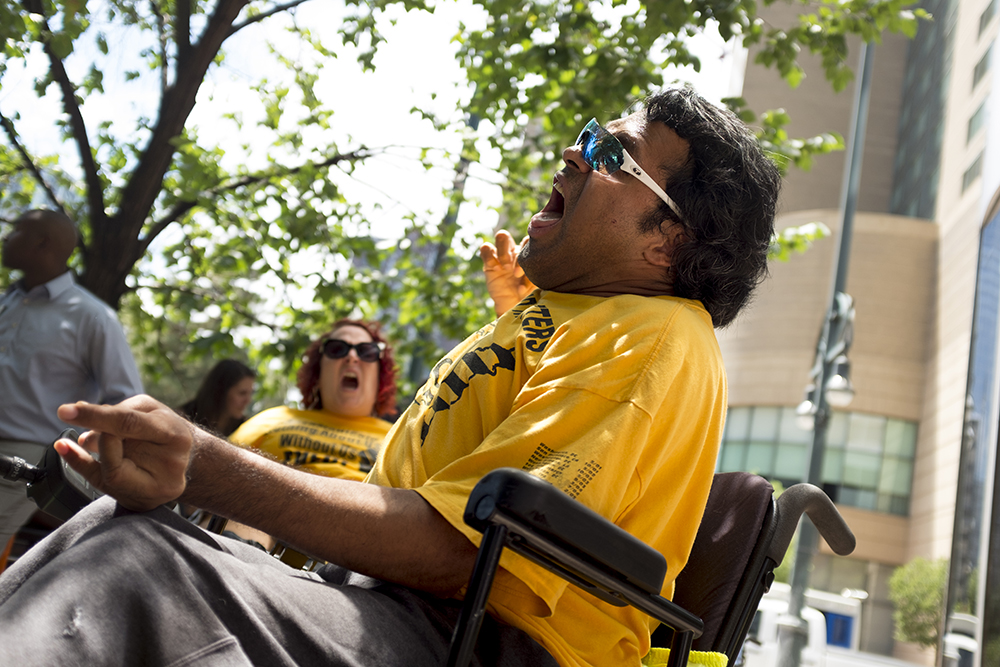 """Jose Torres-Vega screams, """"Kill the bill! Don't kill us!"""" An ADAPT protest against yet another healthcare bill in Washington that could strip Medicaid coverage. Skyline Park, July 27, 2017. (Kevin J. Beaty/Denverite)  adapt; healthcare; denver; colorado; denverite; skyline park; medicaid; kevinjbeaty;"""
