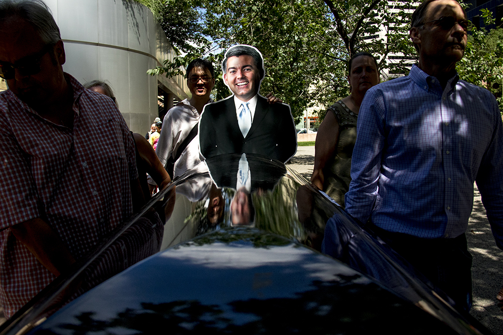 A cutout of Cory Gardner is reflected in a casket as it circles the building containing his office. An ADAPT protest against yet another healthcare bill in Washington that could strip Medicaid coverage. Skyline Park, July 27, 2017. (Kevin J. Beaty/Denverite)