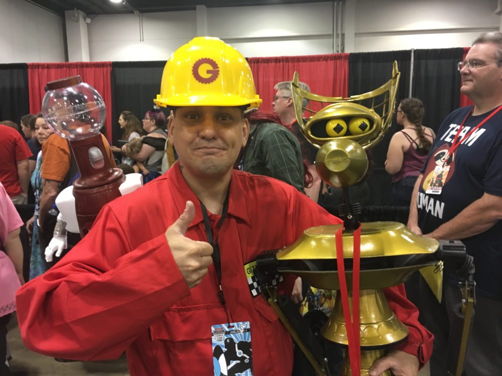 Phillipe LeHardy, in his Gizmodic Institute uniform, poses with his homemade Tom Servo and Crow T. Robot puppets while waiting in line to meet Felicia Day. (Dave Burdick/Denverite)