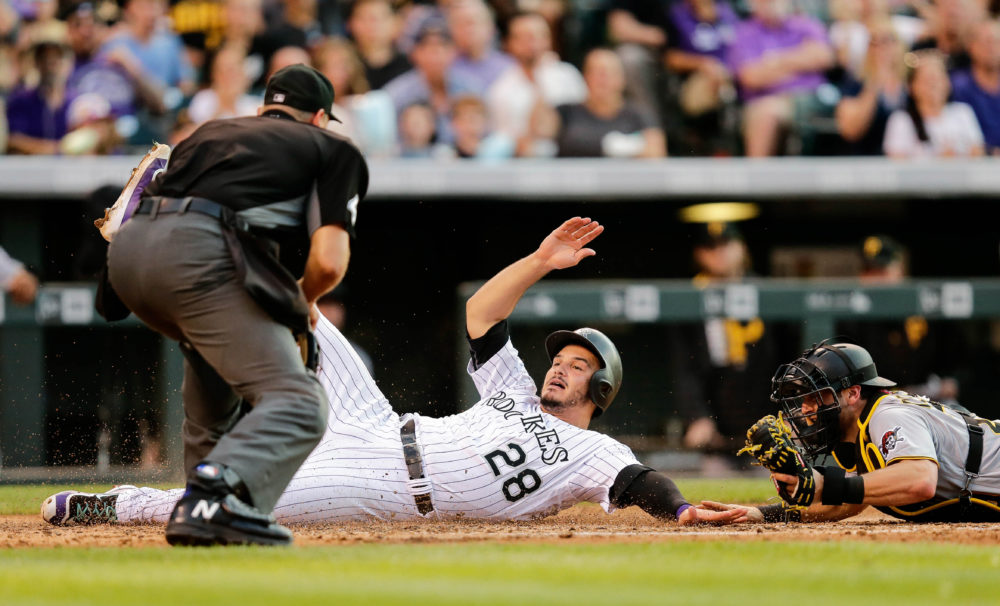 Home plate umpire Chad Fairchild (4) watches as Pittsburgh Pirates catcher Francisco Cervelli (29) tags out Colorado Rockies third baseman Nolan Arenado (28) in the fifth inning at Coors Field. (Isaiah J. Downing/USA TODAY Sports)
