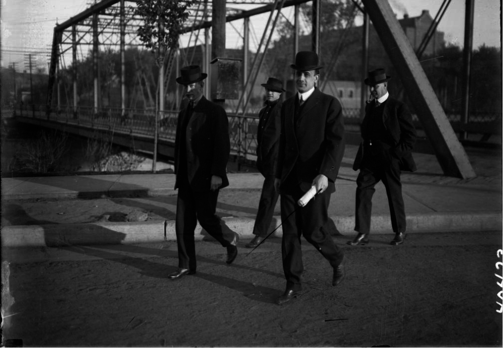 Four men walk near the Colfax bridge over Cherry Creek between 1905 and 1915. (Harry Mellon Rhoads/Western History & Genealogy Dept./Denver Public Library)