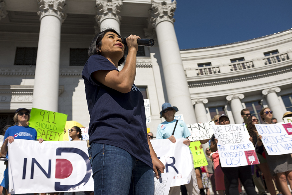 Colorado People's Alliance organizer, Ana Rodriguez, speaks at a rally on the steps of the City and Couny Building before a Denver City Council hearing on immigration policy begins, Aug. 2, 2017. (Kevin J. Beaty/Denverite)  immigration; undocumented; city and council building; denver; colorado; denverite; city council; kevinjbeaty;