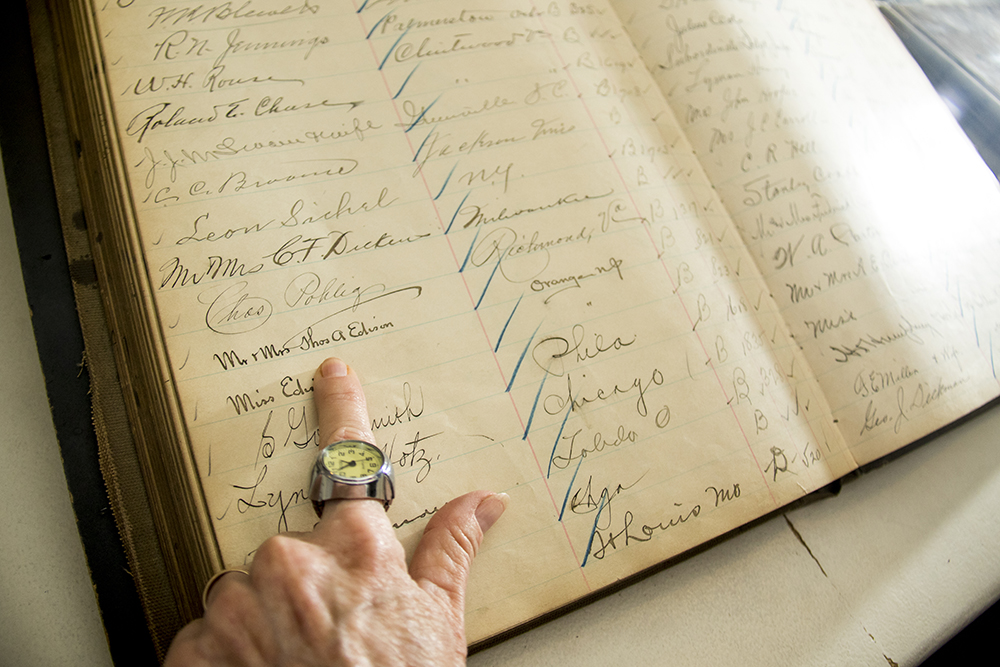 The Brown Palace Hotel's historian Debra Faulkner shows Thomas Edison's signature in an original hotel guest book, Aug. 4, 2017. (Kevin J. Beaty/Denverite)  brown palace hotel; denver; colorado; denverite; kevinjbeaty;