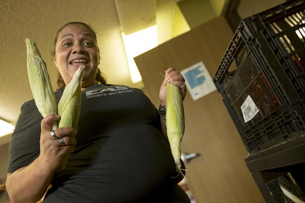 Lorena Santa Cruz shows off corn in the Denver Inner City Parish's food bank, Lincoln Park. (Kevin J. Beaty/Denverite)  lincoln park; denver; colorado; denverite; kevinjbeaty; church;