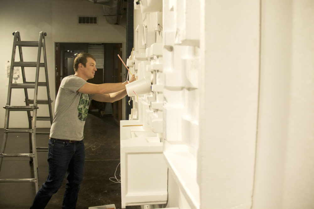 Billy Friebele sets up an installation inside ReCreative on Santa Fe Drive, Aug. 4, 2017. (Kevin J. Beaty/Denverite)  art district on santa fe; recreative; diy; gallery;