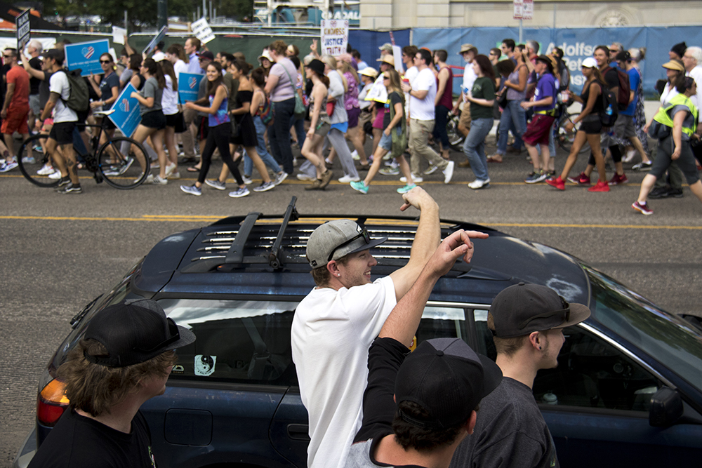 Young men raise middle fingers to the marchers. A rally in response to white supremacist protests in Charlottesville, VA, Aug. 13, 2017. (Kevin J. Beaty/Denverite)  protest; charlottesville; rally; denver; colorado; kevinjbeaty; denverite; colfax