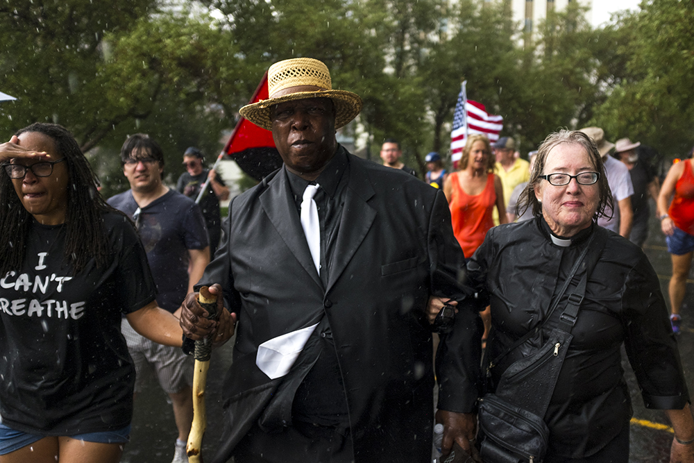 New Covenant Alpha and Omega's Pastor Terrence Hughes walks in the rain with marchers. A rally in response to white supremacist protests in Charlottesville, VA, Aug. 13, 2017. (Kevin J. Beaty/Denverite)  protest; charlottesville; rally; denver; colorado; kevinjbeaty; denverite; capitol