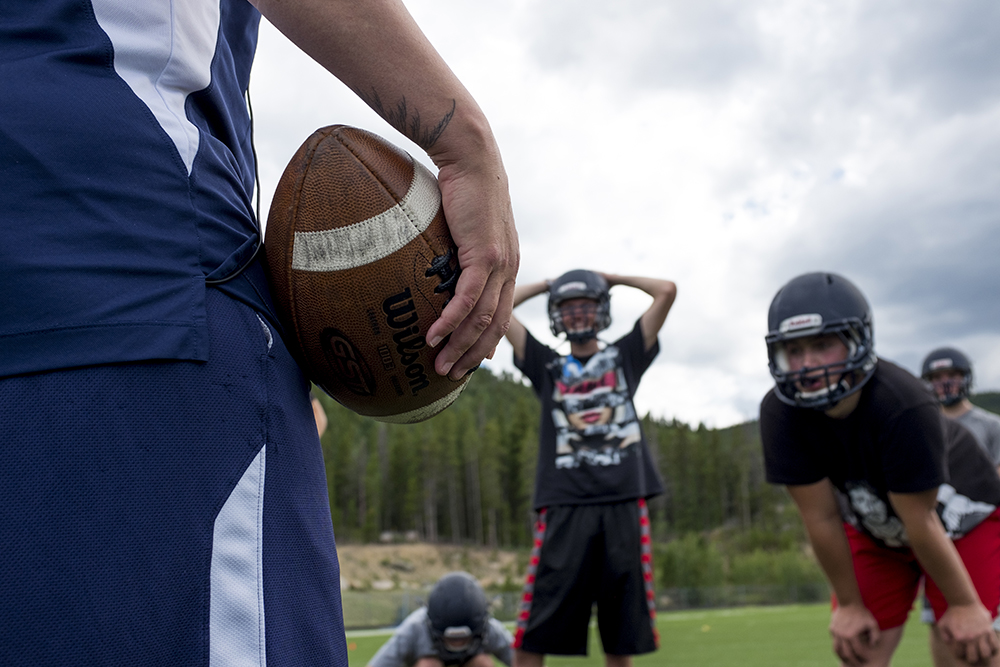 Coach Beth Buglione pretends to spike the ball during defense practice. Nederland Middle-High School's varsity football practice, Aug. 15, 2017. (Kevin J. Beaty/Denverite)  high school football; sports; nederland; Beth Buglione; Nederland Middle-High School;