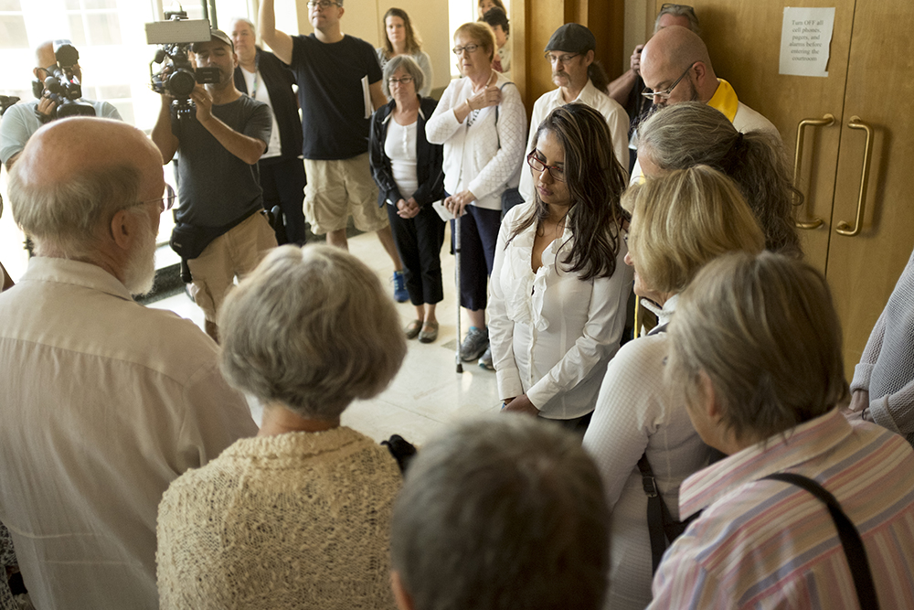 Ingrid Encalada Latorre prays with supporters before her second post-conviction hearing at the Jefferson County Courthouse, Aug. 16, 2017. (Kevin J. Beaty/Denverite)  immigration; undocumented; jefferson county courthouse; denver; colorado; denverite; kevinjbeaty;